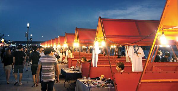 Pessoas Passeando No Mercado Ao Ar Livre, Que Oferece Uma Variedade De Produtos, Desde Simples Acessórios A Perfumes Sólidos. Foto: Jim Min-Ji.