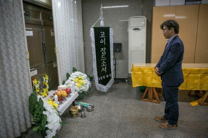 Park Jin-Ok Faz Um Tributo Silencioso Na Frente De Um Refrigerador Em Um Necrotério, Onde Um Corpo Não Reclamado Era Mantido.
