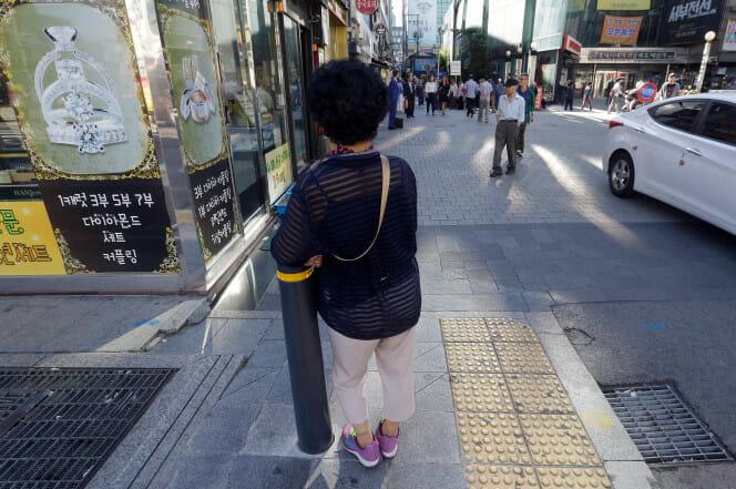 Uma Senhora Idosa Encontra-Se Na Pequena Praça Em Frente O Teatro Piccadilly Em Seul, Coreia Do Sul – Um Lugar Onde Prostitutas Idosas Procuram Por Clientes Abertamente Para Sexo Em Hotéis Da Proximidade.