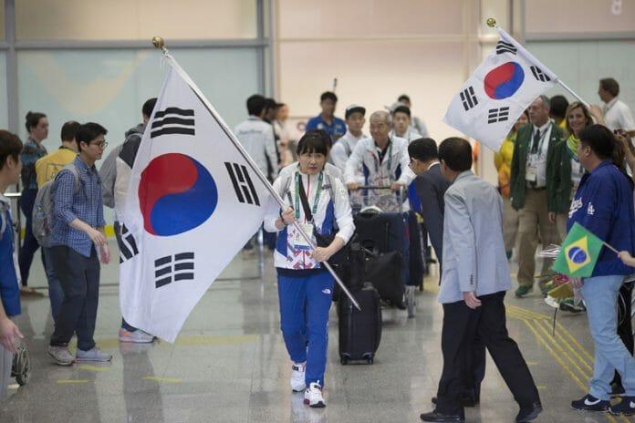 A Atleta Yongram Com A Bandeira Da Coreia Do Sul Na Chegada Da Primeira Parte Da Delegação Do País No Rio De Janeiro. Foto: Korea Times/Ap-Yonhap
