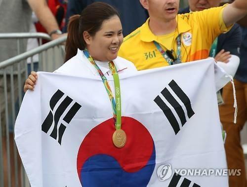 A Golfista Park In-Bee Exibe A Medalha De Ouro Junto À Bandeira Sul Coreana