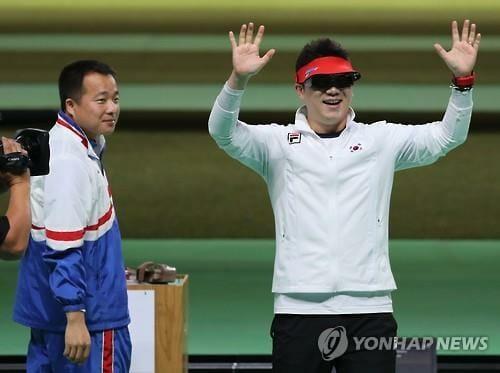 Kim Song-Guk Observa O Sul-Coreano Comemorar Após Vencer A Prova De Tiro Esportivo Na Categoria Pistola 50M. Foto: Yonhap