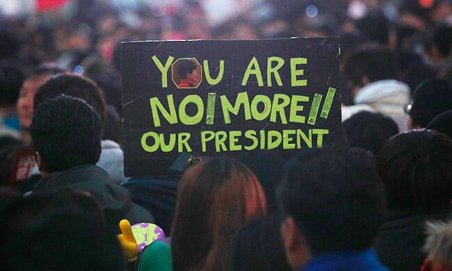 Manifestante Segura Uma Placa Com Mensagem Em Inglês. / Yonhap