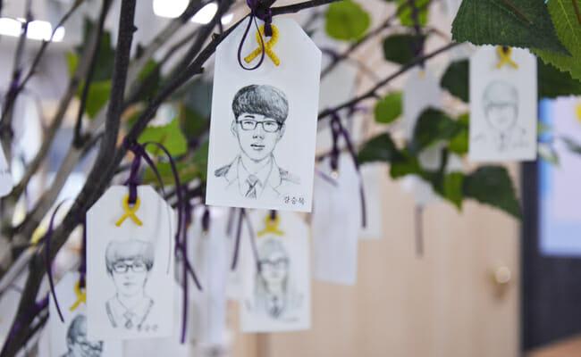 Caricaturas Das 250 Vítimas Penduradas Em Uma Árvore Com Fitas Amarelas – Um Símbolo Comemorativo Para Aqueles Que Morreram No Desastre Do Naufrágio De Sewol – Presas A Imagem De Cada Estudante Para Honra-Los/ Korea Time Por Dam-Young Hong.