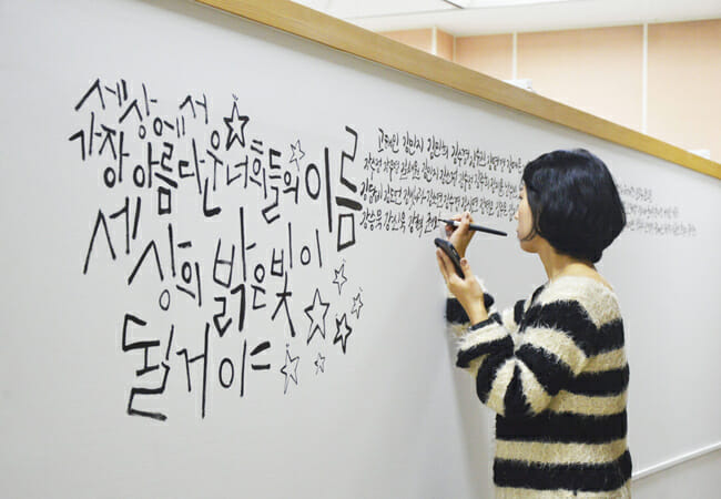 """Su-Yeon Heo, Uma Calígrafa, Escreve O Nome Das 250 Vítimas Da Escola Danwon Em Umas Das Paredes Do Segundo Andar Da Secretária De Educação De Ansan. """"Eu Chamo Cada Um Pelos Seus Nomes Enquanto Escrevo.""""Su-Yeon. """"Desse Modo, Não Esquecerei Das Vítimas.""""/ Korea Times Por Dam-Young Hong."""
