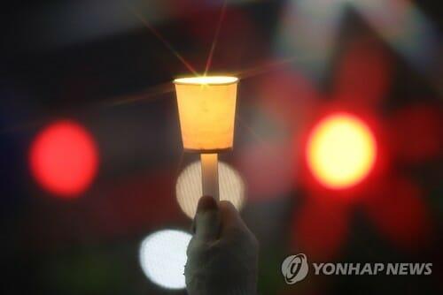 Um Manifestante Levanta Uma Vela Na Praça Gwanghwamun, No Centro De Seul, Em 26 De Novembro De 2016, Enquanto Participava De Uma Manifestação Pedindo A Renúncia Do Presidente Park Geun-Hye. (Yonhap)