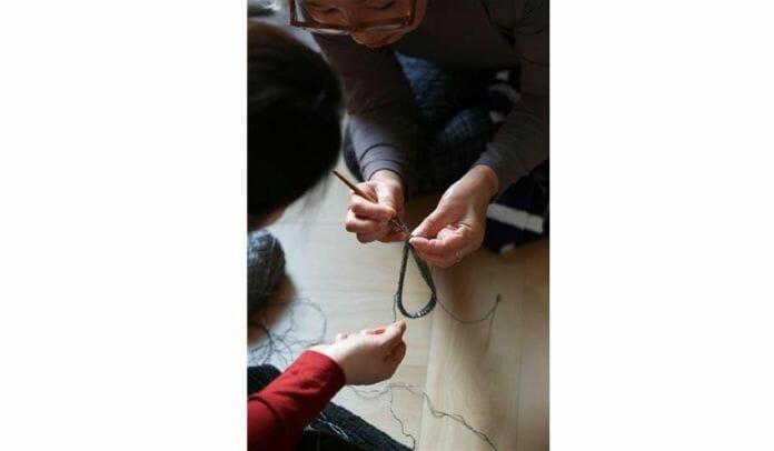 Uma Voluntária Ensinando À Uma Das Mães Como Fazer Crochê.