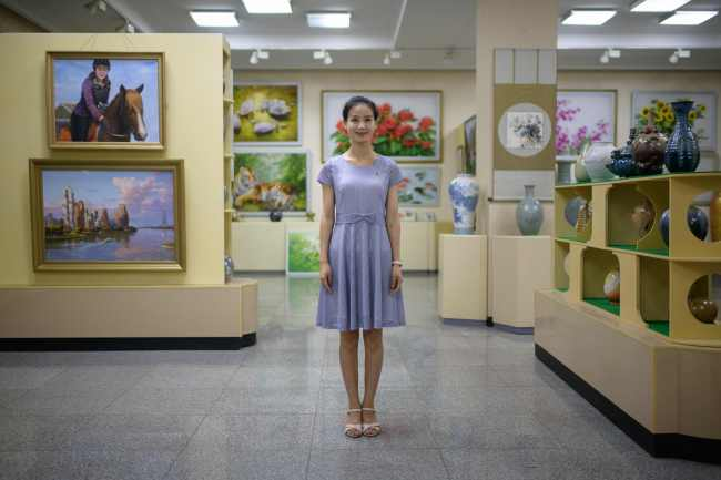 In A Photo Taken On July 25, 2018 Shop Assistant Pak Um Hyang (24) Poses For A Portrait In A Shop At The Mansudae Art Studio In Pyongyang. Founded In 1959 By Kim Il-Sung, Mansudae Employs 700 Artists Who Are Ranked In A Clearly Defined Hierarchy. They Work Within A Vast Complex The Size Of A Small Village With Hundreds Of Studios Housed Inside Cavernous Cement Buildings. / Afp Photo / Ed Jones/2018-07-31 15:20:18/