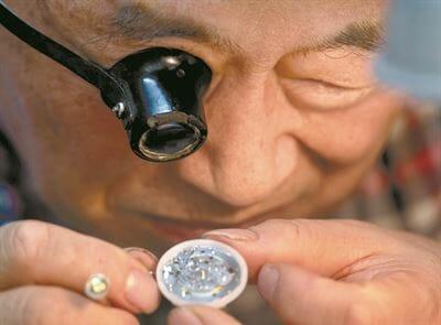 Park Jong-Hyun Examinando Um Relógio. Foto: Shim Hyun-Chul / Korea Times